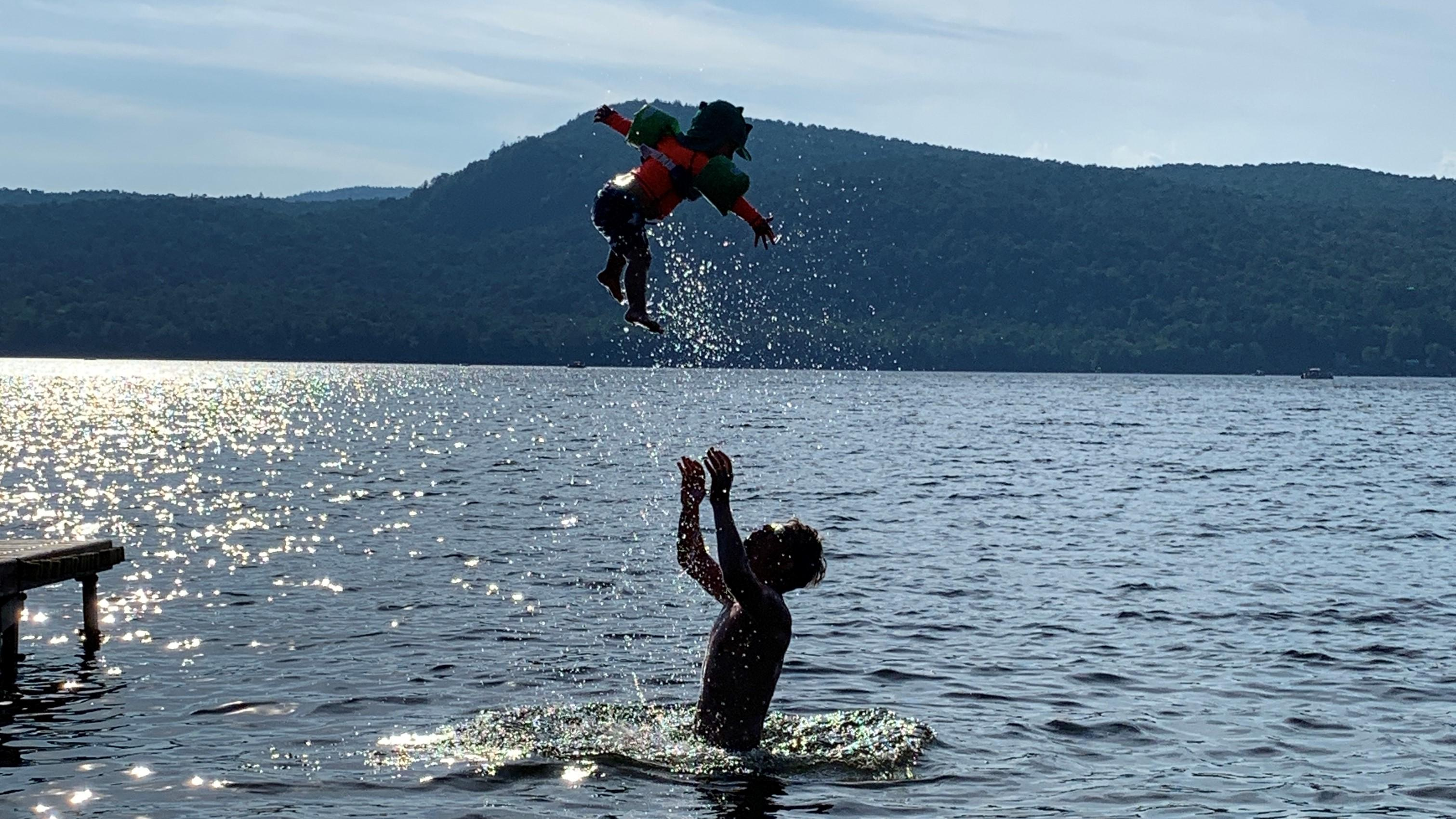 Man throwing kid into air while swimming in lake