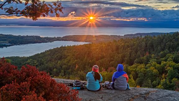 Hikers on a summit watching the sun rise.